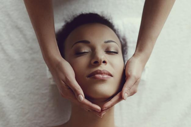 Afroamerikanerin, die eine entspannende massage am spa erhält Kostenlose Fotos