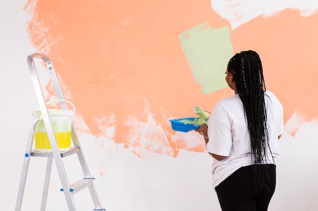 Afroamerikanerin, die eine wohnung malt. renovierungs-, reparatur- und renovierungskonzept.