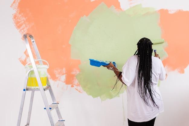 Afroamerikanerin, die eine wohnung malt.