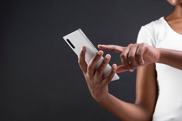 Afroamerikanerin, die ihr smartphone benutzt