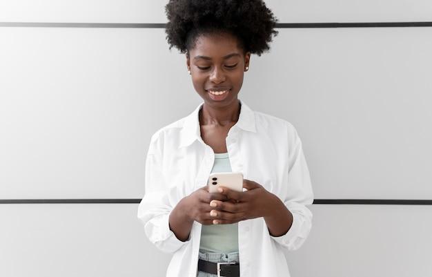 Afroamerikanerin, die jemandem auf ihrem smartphone eine sms schreibt