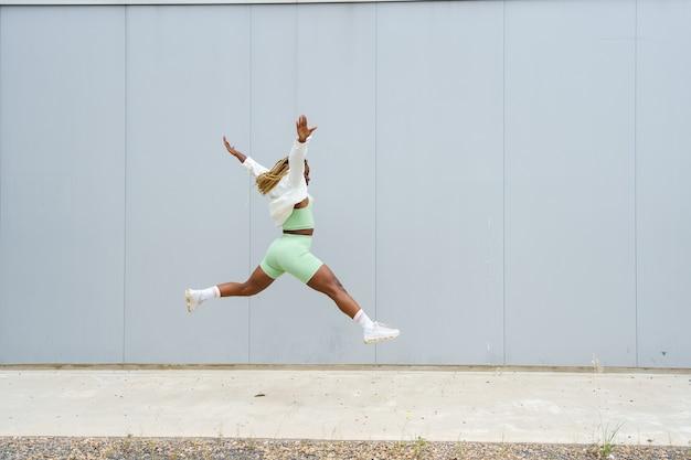 Afroamerikanerin, die neben einer stadtmauer frei springt, trägt ein oberteil und shorts