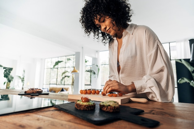 Afroamerikanerin, die tomaten schneidet, die das frühstück in der küche vorbereitet