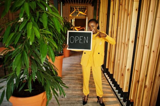 Afroamerikanerin hält offenes willkommensschild im modernen café-café bereit für den service, restaurant, einzelhandelsgeschäft, kleinunternehmer.