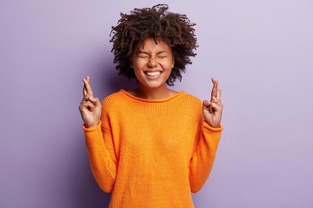 Afroamerikanerin im orangefarbenen pullover