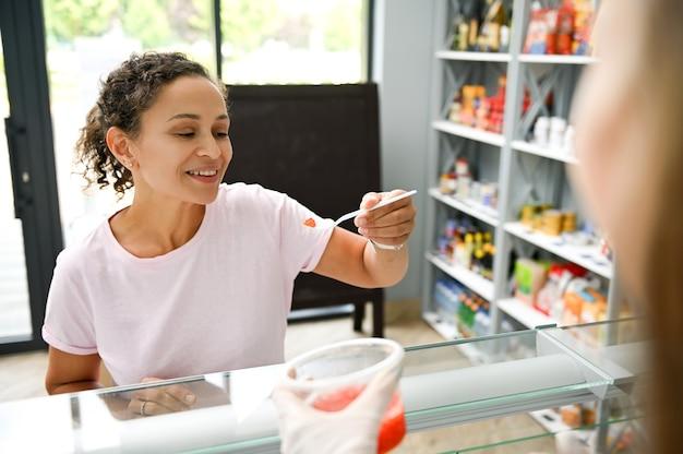 Afroamerikanerin, käuferkunde, die im fischladen einen lachsroten kaviar probiert.