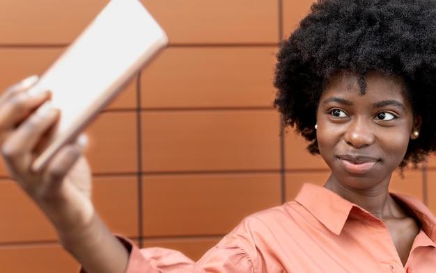 Afroamerikanerin macht ein selfie mit ihrem smartphone