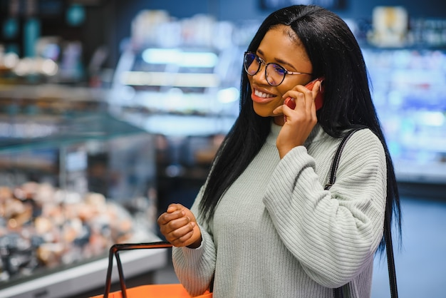 Afroamerikanerin mit einkaufswagen im supermarkt spricht mit dem handy.