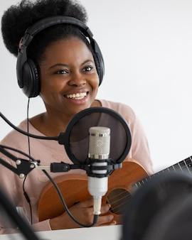 Afroamerikanerin mit kopfhörern und mikrofon, die einen podcast in einem tonstudio aufnimmt