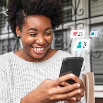 Afroamerikanerin überprüft social media auf einem telefon