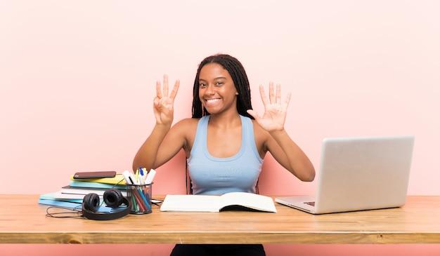 Afroamerikanerjugendlich-kursteilnehmermädchen mit dem langen umsponnenen haar an ihrem arbeitsplatz, der acht mit den fingern zählt