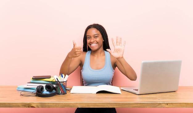 Afroamerikanerjugendlich-kursteilnehmermädchen mit dem langen umsponnenen haar an ihrem arbeitsplatz, der sechs mit den fingern zählt