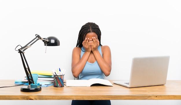 Afroamerikanerjugendlich-kursteilnehmermädchen mit dem langen umsponnenen haar an ihrem arbeitsplatz mit müdem und krankem ausdruck