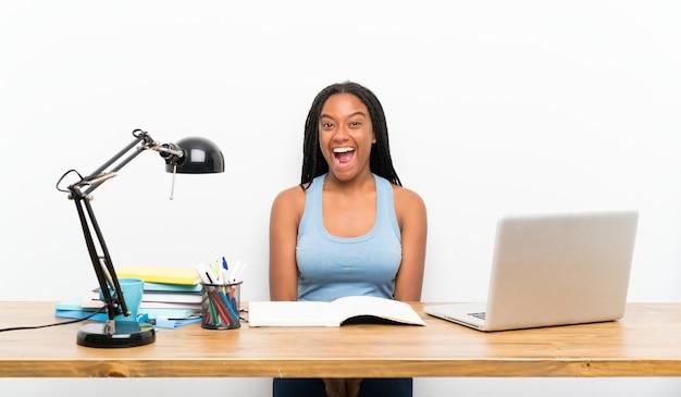 Afroamerikanerjugendlich-kursteilnehmermädchen mit dem langen umsponnenen haar an ihrem arbeitsplatz mit überraschungsgesichtsausdruck