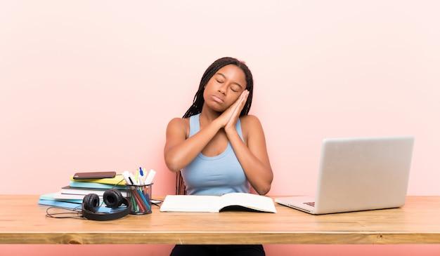 Afroamerikanerjugendlich-kursteilnehmermädchen mit dem langen umsponnenen haar an ihrem arbeitsplatz schlafgeste im entzückenden ausdruck machend