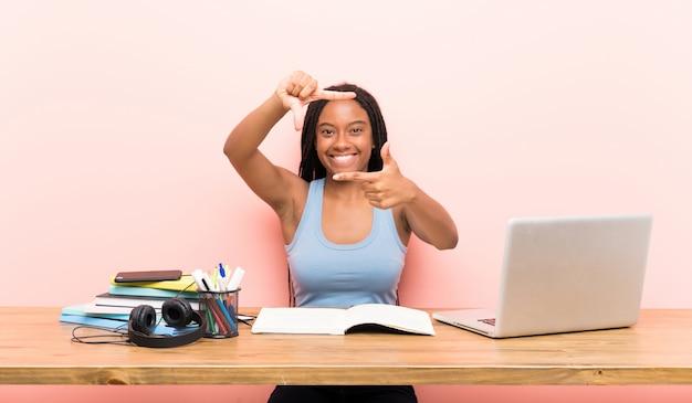 Afroamerikanerjugendlich-kursteilnehmermädchen mit dem langen umsponnenen haar an ihrem arbeitsplatzfokussierungsgesicht
