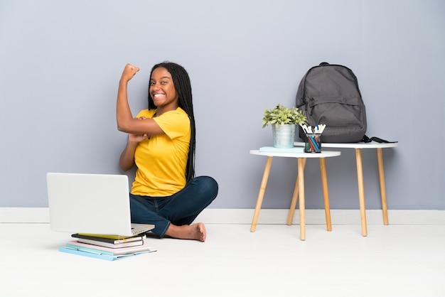 Afroamerikanerjugendlich-kursteilnehmermädchen mit dem langen umsponnenen haar, das auf dem fußboden bildet starke geste sitzt