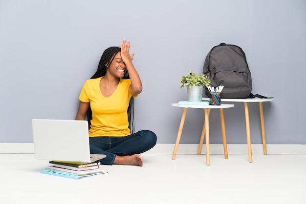 Afroamerikanerjugendlich-kursteilnehmermädchen mit dem langen umsponnenen haar, das auf dem fußboden hat zweifel mit verwirren gesichtsausdruck sitzt