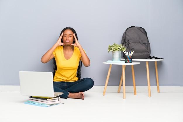 Afroamerikanerjugendlich-kursteilnehmermädchen mit dem langen umsponnenen haar, das auf dem fußboden unglücklich und frustriert sitzt