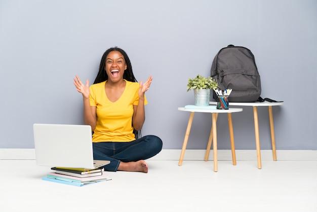 Afroamerikanerjugendlich-kursteilnehmermädchen mit dem langen umsponnenen haar, das auf dem fußboden unglücklich und mit etwas frustriert sitzt