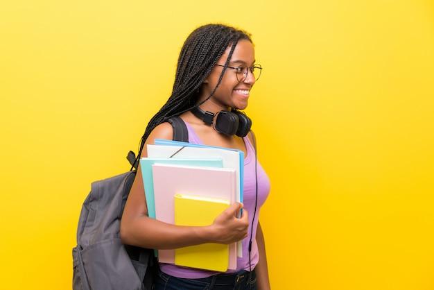 Afroamerikanerjugendlich-kursteilnehmermädchen mit dem langen umsponnenen haar über der getrennten gelben wand, die zur seite schaut