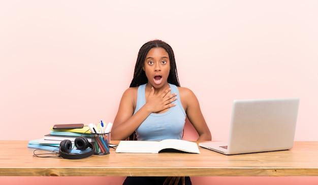 Afroamerikanerjugendlich-studentenmädchen mit dem langen umsponnenen haar an ihrem arbeitsplatz beim schauen überrascht und entsetzt