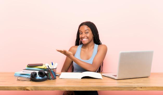 Afroamerikanerjugendlich-studentenmädchen mit dem langen umsponnenen haar an ihrem arbeitsplatz, der eine idee darstellt
