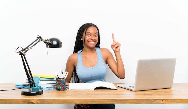Afroamerikanerjugendlich-studentenmädchen mit dem langen umsponnenen haar an ihrem arbeitsplatz, der einen finger im zeichen des besten zeigt und anhebt