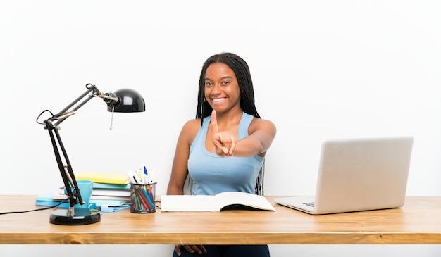 Afroamerikanerjugendlich-studentenmädchen mit dem langen umsponnenen haar an ihrem arbeitsplatz, der einen finger zeigt und anhebt