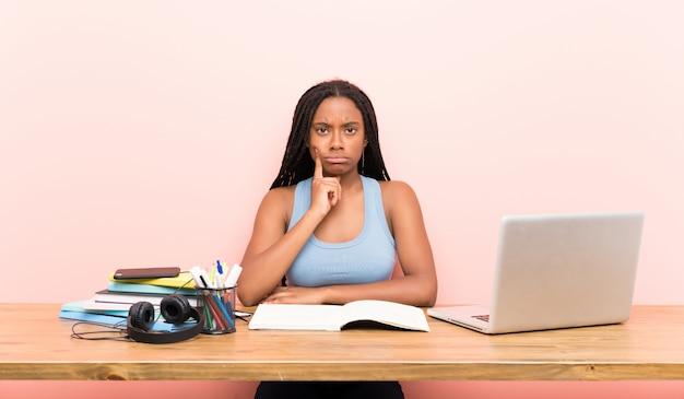 Afroamerikanerjugendlich-studentenmädchen mit dem langen umsponnenen haar an ihrem arbeitsplatz, der front schaut