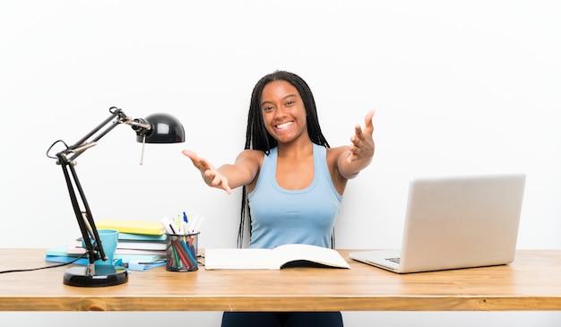 Afroamerikanerjugendlich-studentenmädchen mit dem langen umsponnenen haar an ihrem arbeitsplatz, der sich darstellt und einlädt, mit der hand zu kommen