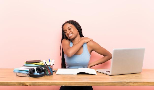Afroamerikanerjugendlich-studentenmädchen mit dem langen umsponnenen haar an ihrem arbeitsplatz, der unter den schmerz in der schulter leidet