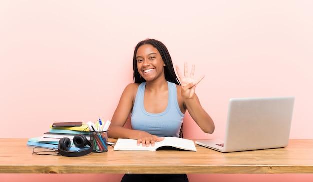 Afroamerikanerjugendlich-studentenmädchen mit dem langen umsponnenen haar an ihrem arbeitsplatz glücklich und vier mit den fingern zählend