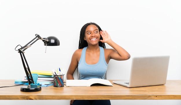 Afroamerikanerjugendlich-studentenmädchen mit dem langen umsponnenen haar an ihrem arbeitsplatz hörend auf etwas
