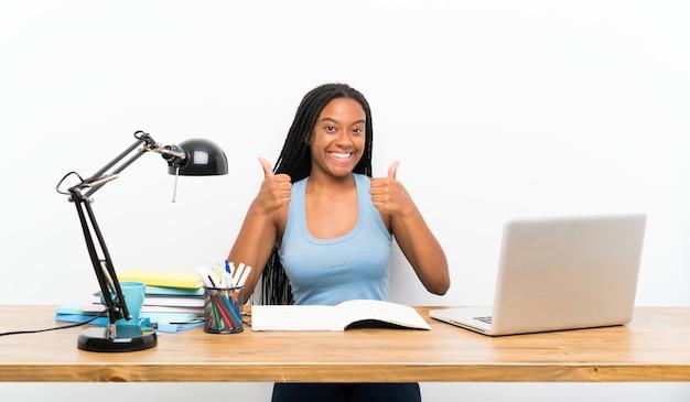 Afroamerikanerjugendlich-studentenmädchen mit dem langen umsponnenen haar an ihrem arbeitsplatz mit den daumen up geste und lächeln