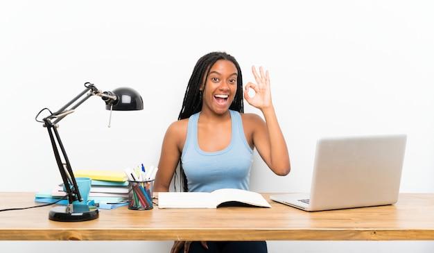 Afroamerikanerjugendlich-studentenmädchen mit dem langen umsponnenen haar an ihrem arbeitsplatz überrascht und okayzeichen zeigend