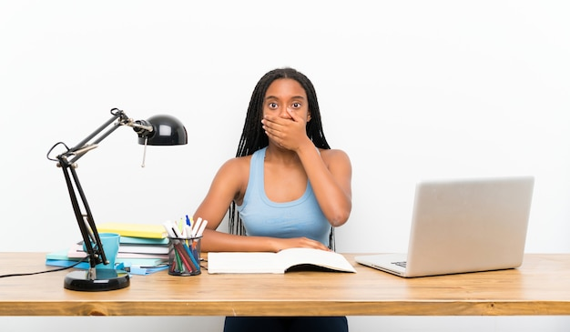 Afroamerikanerjugendlich-studentenmädchen mit dem langen umsponnenen haar an ihrem arbeitsplatzbedeckungsmund mit den händen