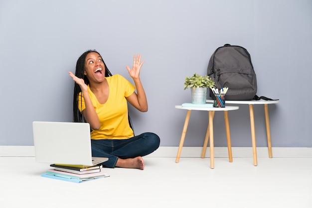 Afroamerikanerjugendlich-studentenmädchen mit dem langen umsponnenen haar, das auf dem boden mit überraschungsgesichtsausdruck sitzt