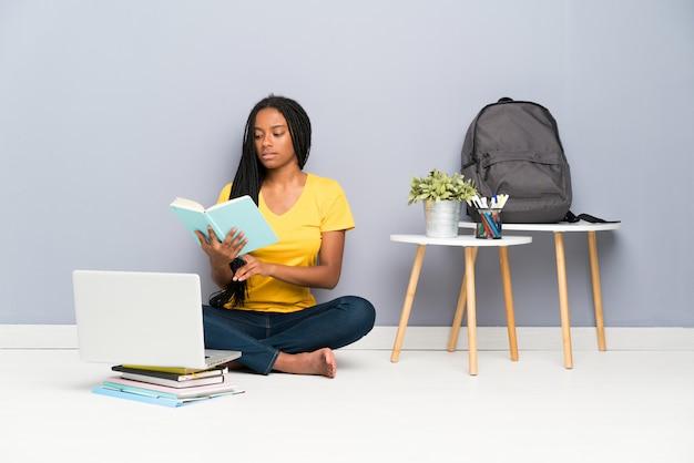 Afroamerikanerjugendlich-studentenmädchen mit dem langen umsponnenen haar, das auf dem boden sitzt und ein buch liest