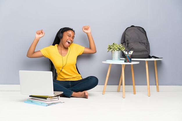 Afroamerikanerjugendlich-studentenmädchen mit dem langen umsponnenen haar, das auf dem boden und dem tanzen sitzt