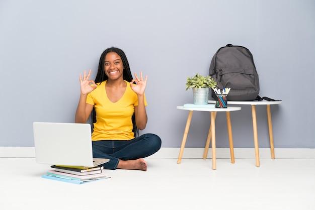 Afroamerikanerjugendlich-studentenmädchen mit dem langen umsponnenen haar, das auf dem boden zeigt ein okayzeichen mit den fingern sitzt