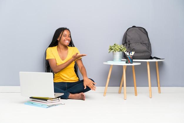 Afroamerikanerjugendlich-studentenmädchen mit dem langen umsponnenen haar, das auf den ausdehnenden händen des bodens sitzt