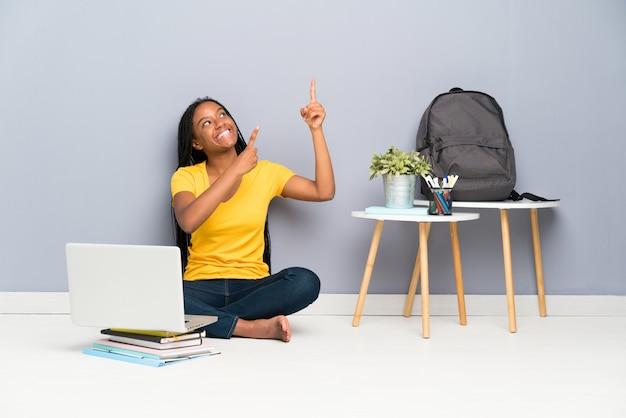Afroamerikanerjugendlich-studentenmädchen mit dem langen umsponnenen haar sitzend auf dem boden, der mit dem zeigefinger eine großartige idee zeigt