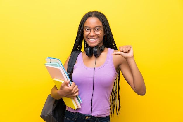 Afroamerikanerjugendlich-studentenmädchen mit dem langen umsponnenen haar über lokalisierter gelber wand stolz und selbstzufrieden
