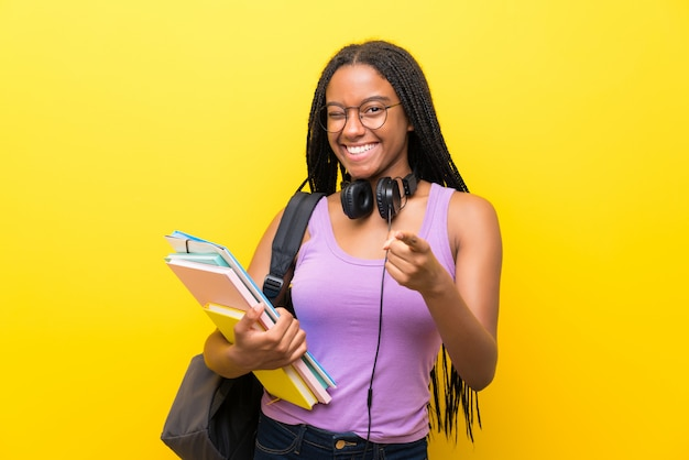 Afroamerikanerjugendlich-studentenmädchen mit dem langen umsponnenen haar über lokalisierter gelber wand zeigt finger auf sie