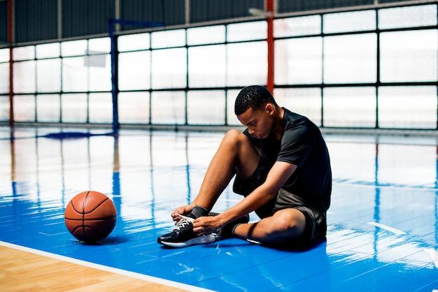 Afroamerikanerjugendlicher, der seine schnürsenkel auf einem basketballplatz bindet