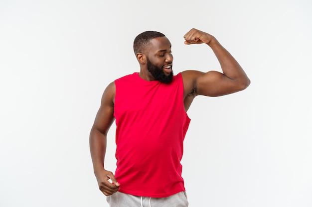 Afroamerikanerjugendlicher zeigt muskeln auf dem arm, lokalisiert auf weiß, studioporträt, übergangsalterkonzept