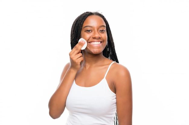 Afroamerikanerjugendlichmädchen mit dem langen umsponnenen haar, das make-up von ihrem gesicht mit baumwollauflage entfernt