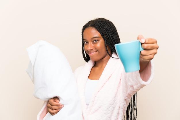 Afroamerikanerjugendlichmädchen mit dem langen umsponnenen haar in den pyjamas über wand und dem halten eines tasse kaffees