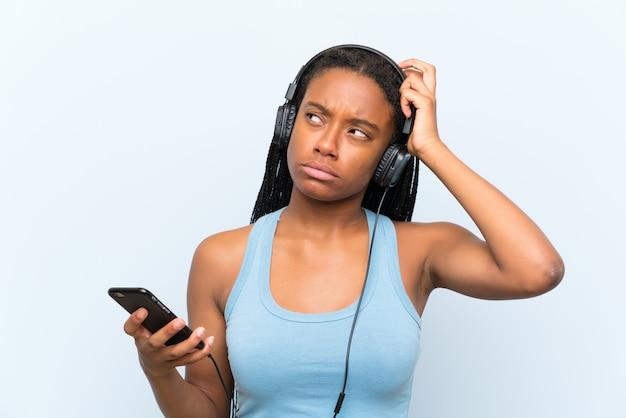 Afroamerikanerjugendlichmädchen mit hörender musik des langen umsponnenen haares mit einem mobile, das zweifel hat und mit verwirren gesichtsausdruck